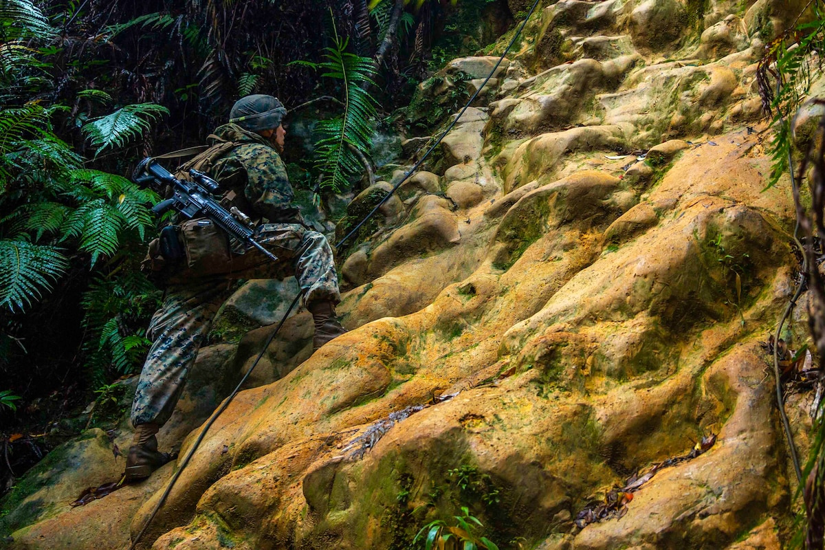 A Marine moves up steep terrain while holding a rope.