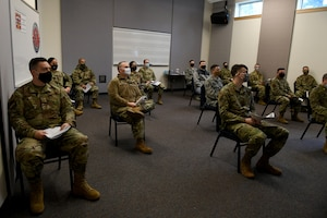 Airmen receive a briefing on the COVID-19 vaccine