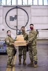 Staff Sgt. Rachelle Bellini, Senior Airman Ruben Moreno, and Senior Airman Nathan Furr, 18th Munitions Unit load crew competition winners stand with their trophy Jan. 8, 2021, on Eielson AFB, Alaska. Every three months there's a load crew competition and the winners of the quarterly challenges will face off at an annual competition. (U.S. Air Force photo by Senior Airman Keith Holcomb)