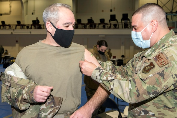 A man in a military uniform applies a small band aid to the arm of another man in military uniform.
