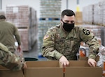 Washington National Guard Pfc. Trenton Choate packs a food box at the Emergency Food Network warehouse in Fife, Wash., on Jan. 6, 2021. The Guard helped pack more than 8,000 emergency food boxes for residents of Pierce County.