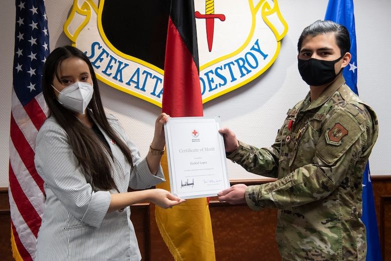 Jocelynn Cobb, Spangdahlem Red Cross regional program manager (left), presents U.S. Air Force Senior Airman Ezekiel Lopez, 52nd Force Support Squadron fitness center journeyman, with the Red Cross Certificate of Merit.