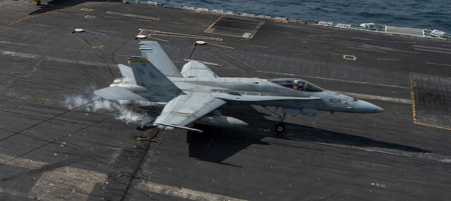 "NORTH ARABIAN SEA (Jan. 9, 2021) An F/A-18C Hornet, from the ""Death Rattlers"" of Marine Fighter Attack Squadron (VMFA) 323, makes an arrested landing on the flight deck of the aircraft carrier USS Nimitz (CVN 68). Nimitz, the flagship of Nimitz Carrier Strike Group, is deployed to the U.S. 5th Fleet area of operations to ensure maritime stability and security in the Central Region, connecting the Mediterranean and Pacific through the Western Indian Ocean and three critical chokepoints to the free flow of global commerce. (U.S. Navy photo by Mass Communication Specialist Seaman Joseph Calabrese)"