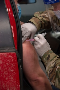 Master Sgt. John McDowell, an aerospace medic with the 157th Medical Group, administers a COVID-19 vaccination in Concord on Jan. 6, 2021.