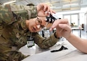 A women in military uniform adjusts a medical device