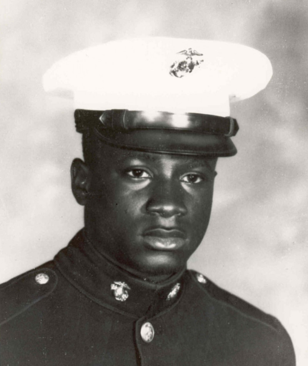 A Marine in dress uniform looks at the camera.