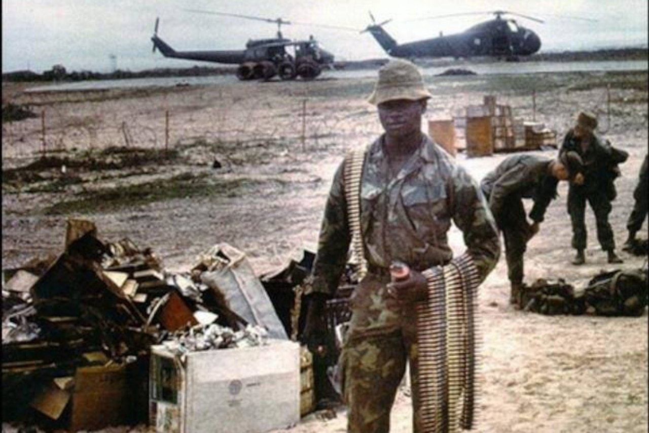 A man in fatigues poses with bands of ammunition as two helicopters and other service members mill around in the background.
