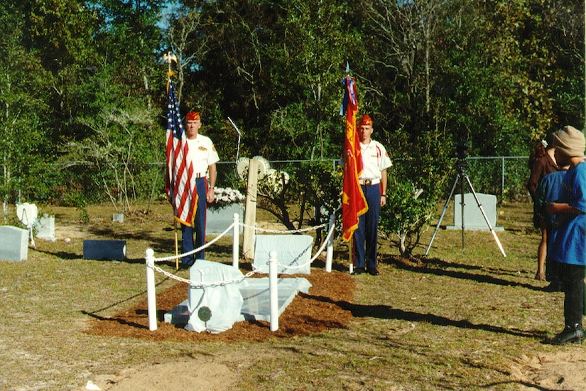 Two Marines hold flags beside a grave cordoned off with a small white chain-link fence.