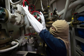 A Sailor trains at an aqueous film forming foam station during a general quarters drill.
