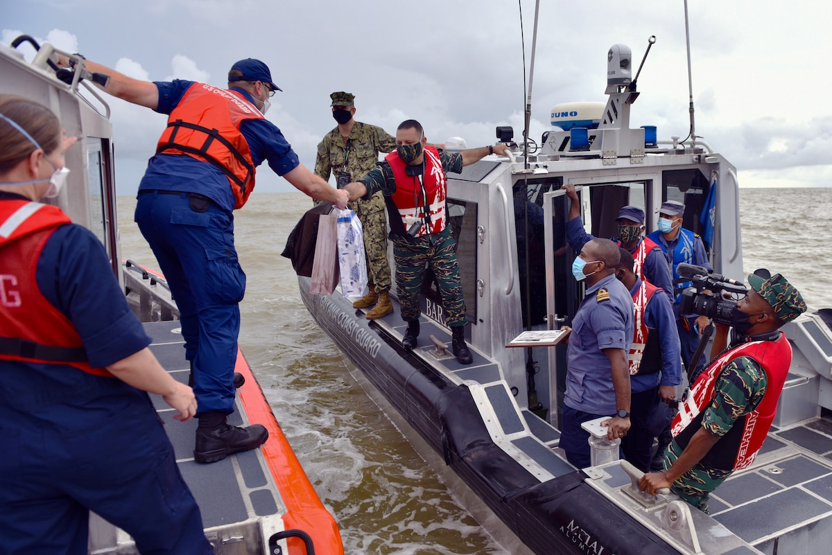 U.S. Coast Guard personnel exchanges gifts with members of the Guyana Coast Guard.