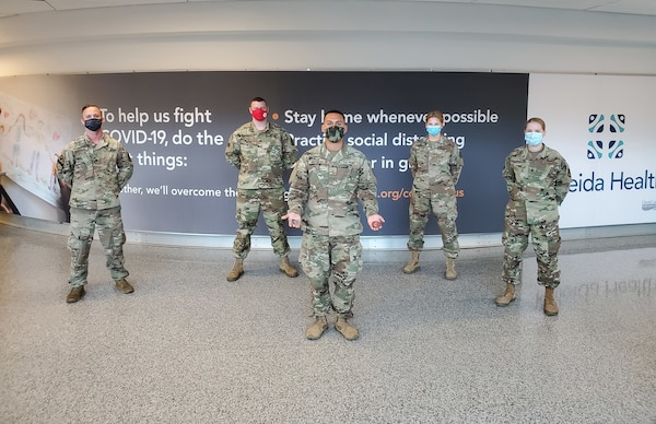 New York Amy National Guard Pfc. Gabriel Martorella, center, assigned to the 719th Transportation Company, is coined by New York National Guard leadership Dec. 31, 2020, after helping a stranded traveler at Buffalo International Airport. Martorella is part of the COVID-19 task force collecting health questionnaires from out-of-state travelers.