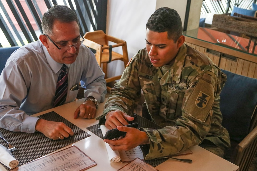 A soldier shares a cell phone image with another man.