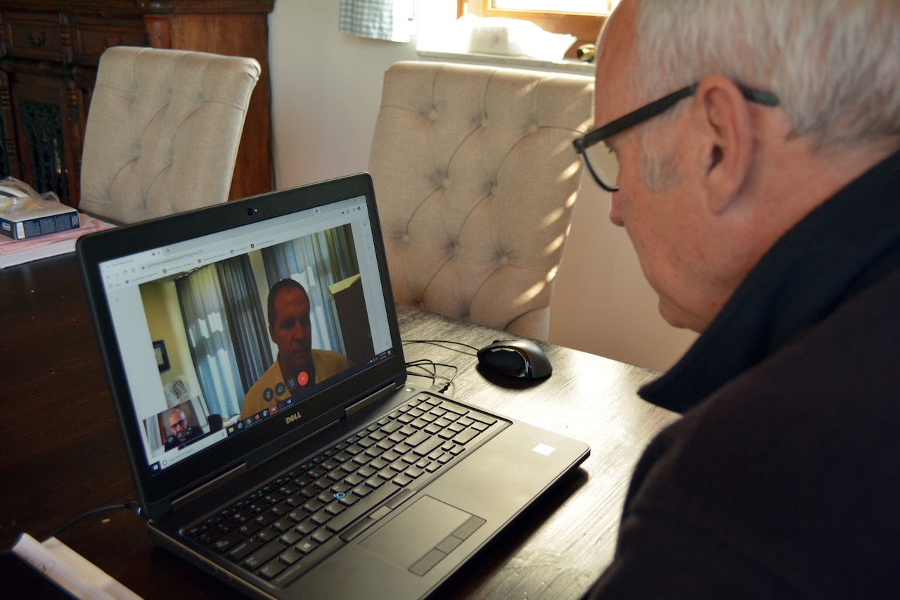 An elderly man speaks with a doctor during a virtual health meeting.