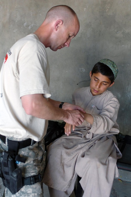 A Soldier gives medical attention to a boy