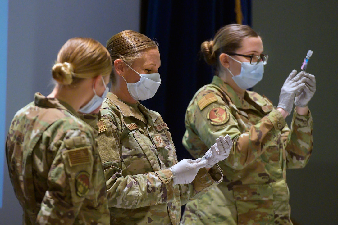 Airmen wearing face masks and gloves fill syringes with COVID-19 vaccines.