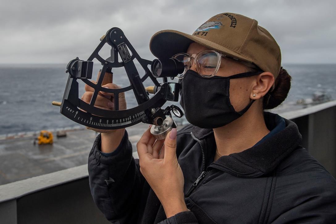 A sailor squints as she looks through a stadimeter.