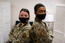 Staff Sgt. Kimberly and Staff Sgt. Laymisha, 432nd Security Forces Squadron Defenders, pose for a photo back to back while looking at the camera.