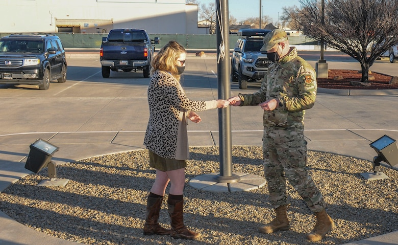 Woman receives coin from Air Force officer.