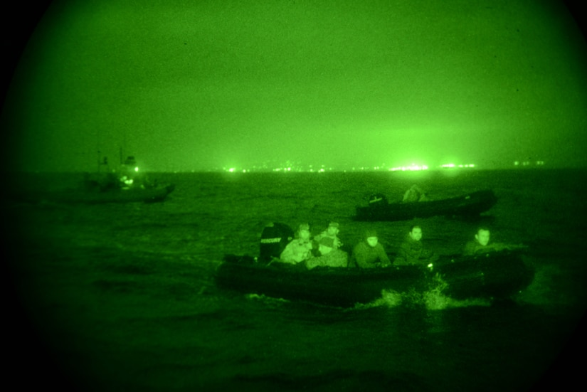 Service members move through the water in inflatable boats.