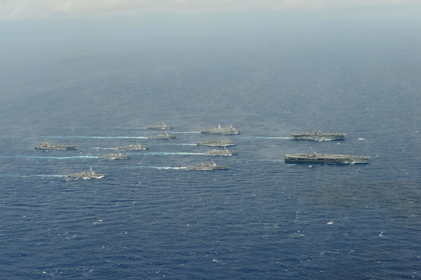 A dozen Navy vessels move through the ocean.