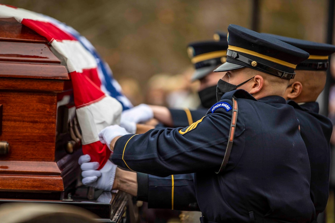 Soldiers drape an American flag over a casket.