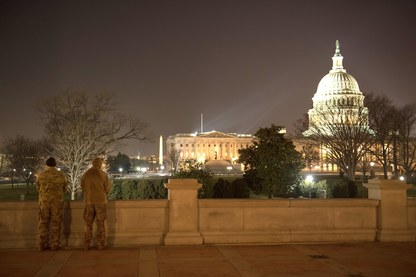 Two soldiers stand guard at night with the Capitol building lit up in the background.
