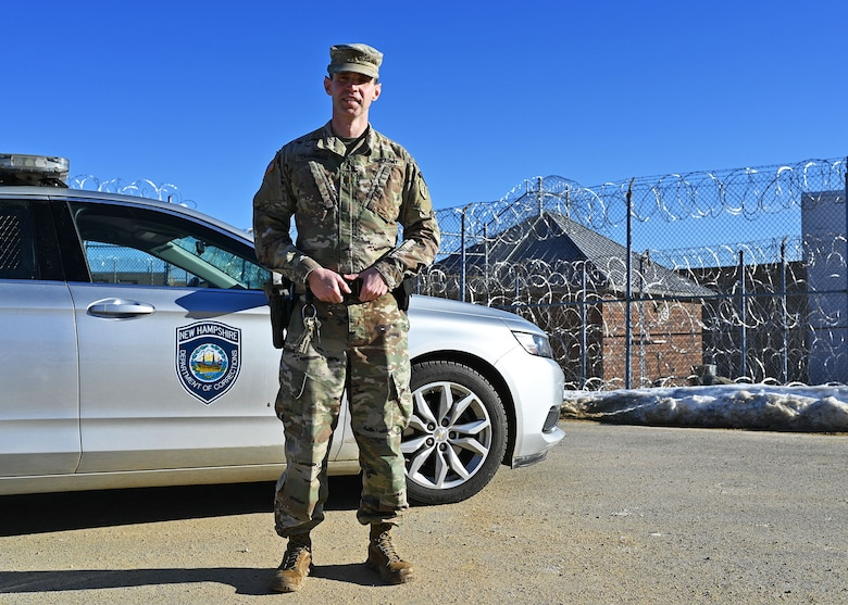1st Lt. James Lawrence, a military police officer with the 237th MP Company, NHARNG, poses with his issued corrections patrol car on the perimeter of the state prison Jan. 10, 2021, in Concord, N.H