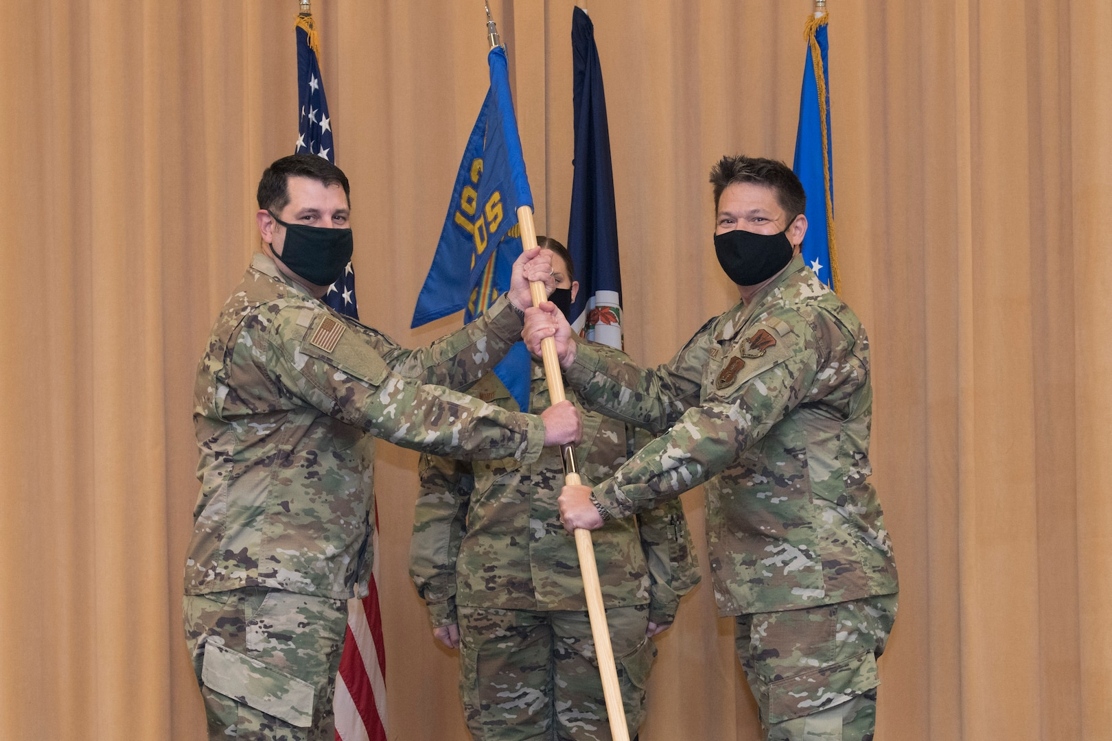 Two Airmen hold a flag during a military change of command ceremony