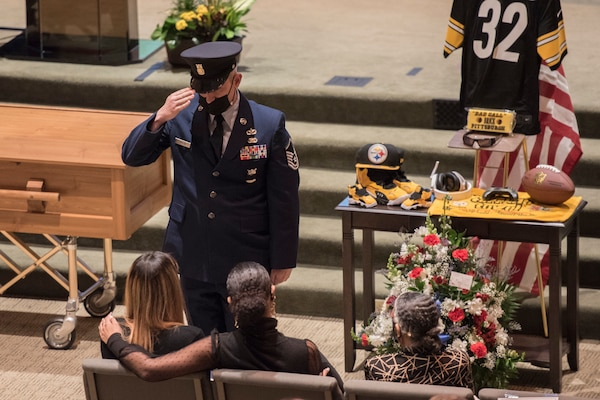Master Sgt. Chris Taylor renders a salute after presenting a flag to London Brown, fiancee to fallen Armen and  firefighter, Senior Airman Logan Young, during funeral services at Victory Church, WInchester, Va., Jan. 7, 2021. Young died while battling an off-base barn fire Dec. 27, 2020.
