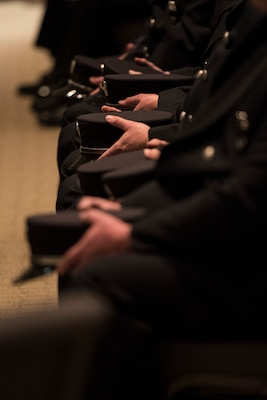 Firefighters sit holding their hats during the funeral service for Senior Airman Logan Young, a 167th Civil Engineering Squadron firefighter who died battling an off-base barn fire on Dec. 27, 2020. The funeral was held at Victory Church in Winchester, Va. Jan. 7, 2021.