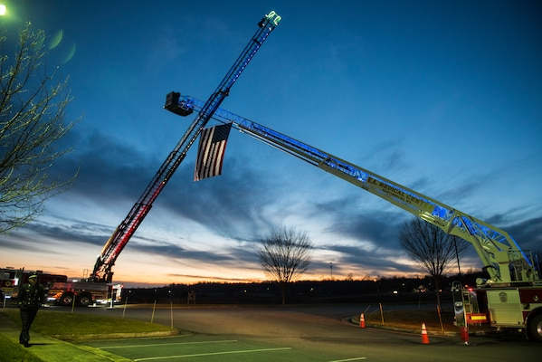 Ladder trucks from the Shepherdstown Fire Department and the Martinsburg Veterans Administration Medical Center Fire Department display an American flag over the entrance to Victory Church in Winchester, Va., Jan. 7, 2021 to honor fallen 167th Airlift Wing Airman and firefighter, Senior Airman Logan Young, who died battling an off-base fire Dec. 27, 2020.