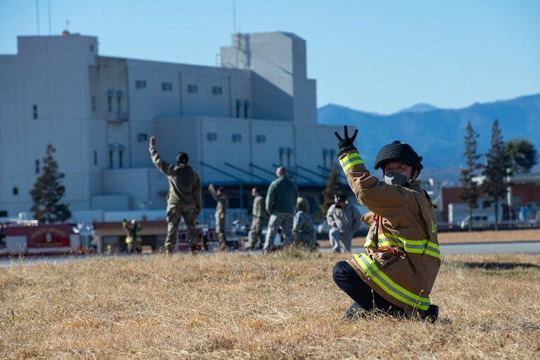 A fire fighter assigned to the 374th Civil Engineer Squadron fire department, gives hand signals to the newly installed flightline BAK-12 barrier, aircraft arresting system (AAS) operators