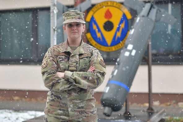 Airman standing in front of building while it is snowing.