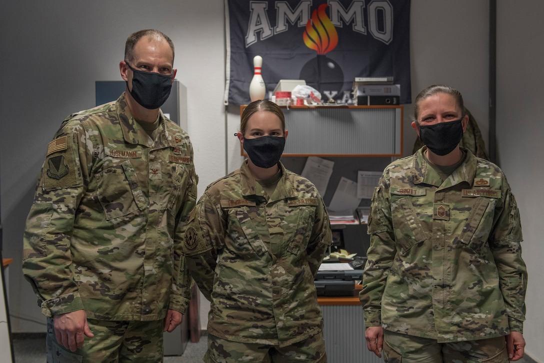 Three Airmen standing in an office.