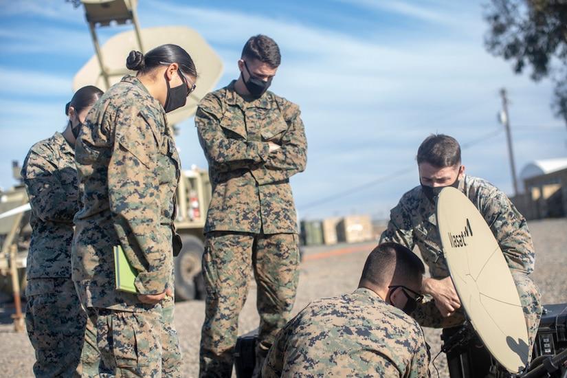 Five Marines work on a satellite dish.