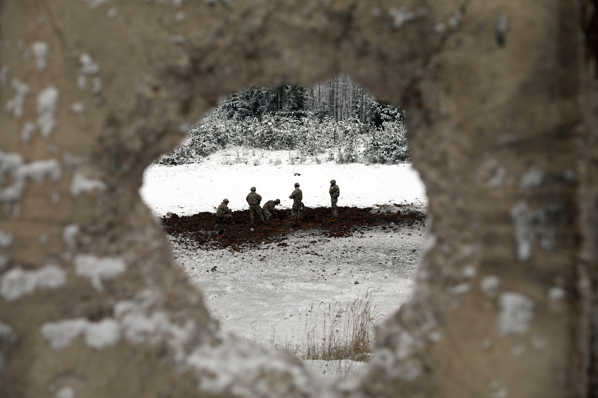 Soldiers seen through a hole in a cement wall work in a field.
