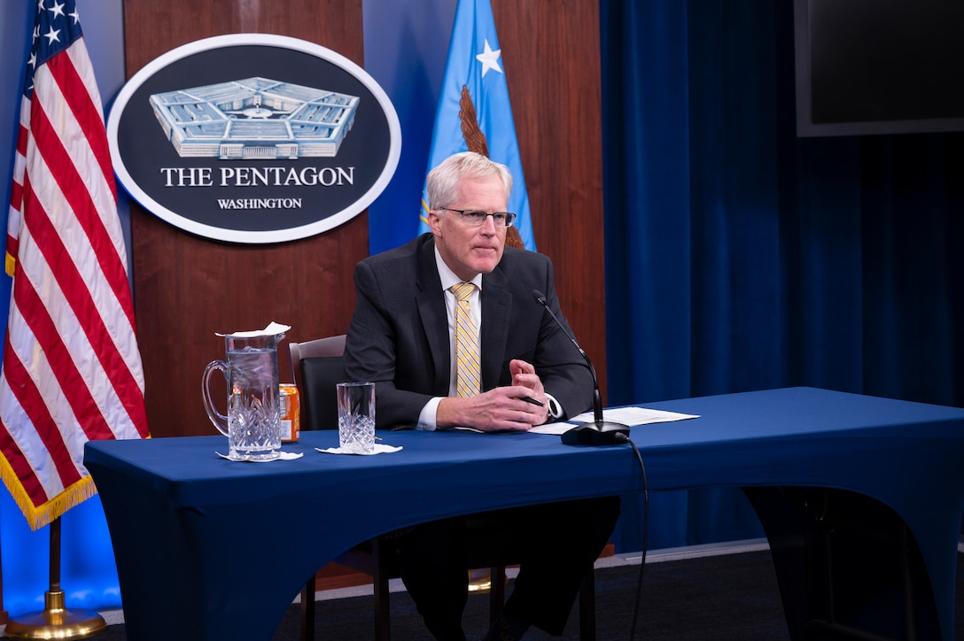 """A man sits at desk and speaks into a microphone. A plaque saying """"The Pentagon"""" and two flags are behind him."""