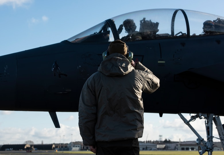 A U.S. Air Force Airman assigned to the 48th Aircraft Maintenance Squadron salutes aircrew as they taxi onto the flightline during Agile Combat Employment training at Royal Air Force Lakenheath, England, Jan. 12, 2021. Exercising elements of ACE enables U.S. Air Forces in Europe to operate from locations with varying levels of capacity and support, ensuring Airmen and aircrews are postured to deliver lethal combat power across the spectrum of military operations. (U.S. Air Force photo by Airman 1st Class Jessi Monte)