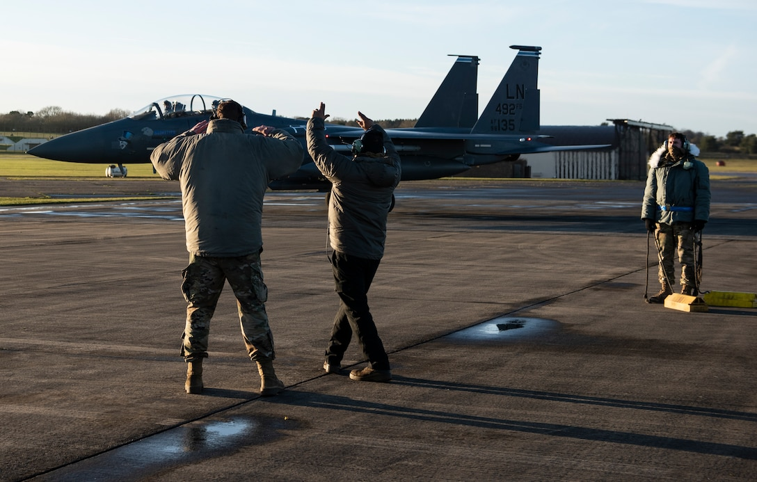 U.S. Air Force Airmen from the 48th Aircraft Maintenance Squadron direct an F-15E Strike Eagle onto the apron during Agile Combat Employment training at Royal Air Force Lakenheath, England, Jan. 12, 2021. Agile Combat Employment capabilities ensure U.S. Air Forces in Europe, along with allies and partners, are ready for potential last minute contingencies by allowing forces to operate from locations with varying levels of capacity and support. (U.S. Air Force photo by Airman 1st Class Jessi Monte)