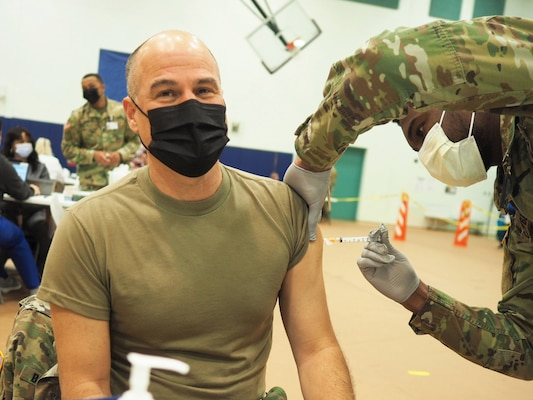 A man in a mask receives a shot from a soldier.