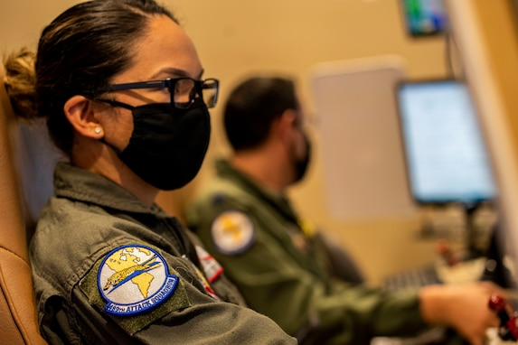 An airman looks at her monitors in a simulator before a training sortie.