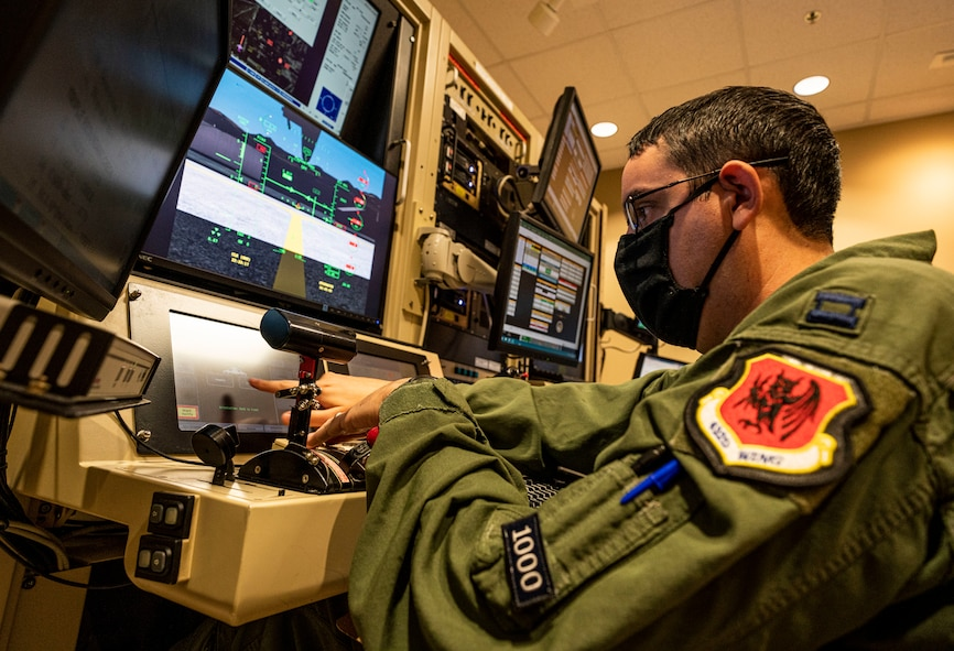 A pilot points at one of his monitors in a simulator.