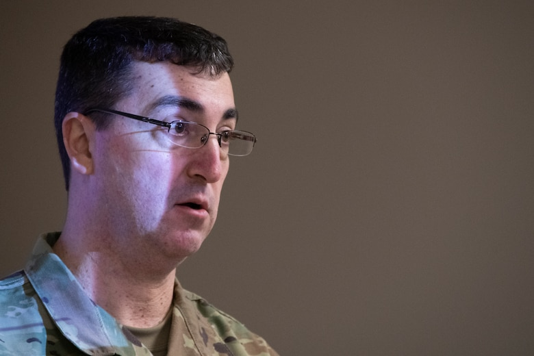 Close up shot of Airman giving a briefing. Light from the overhead projector reflects off his face.