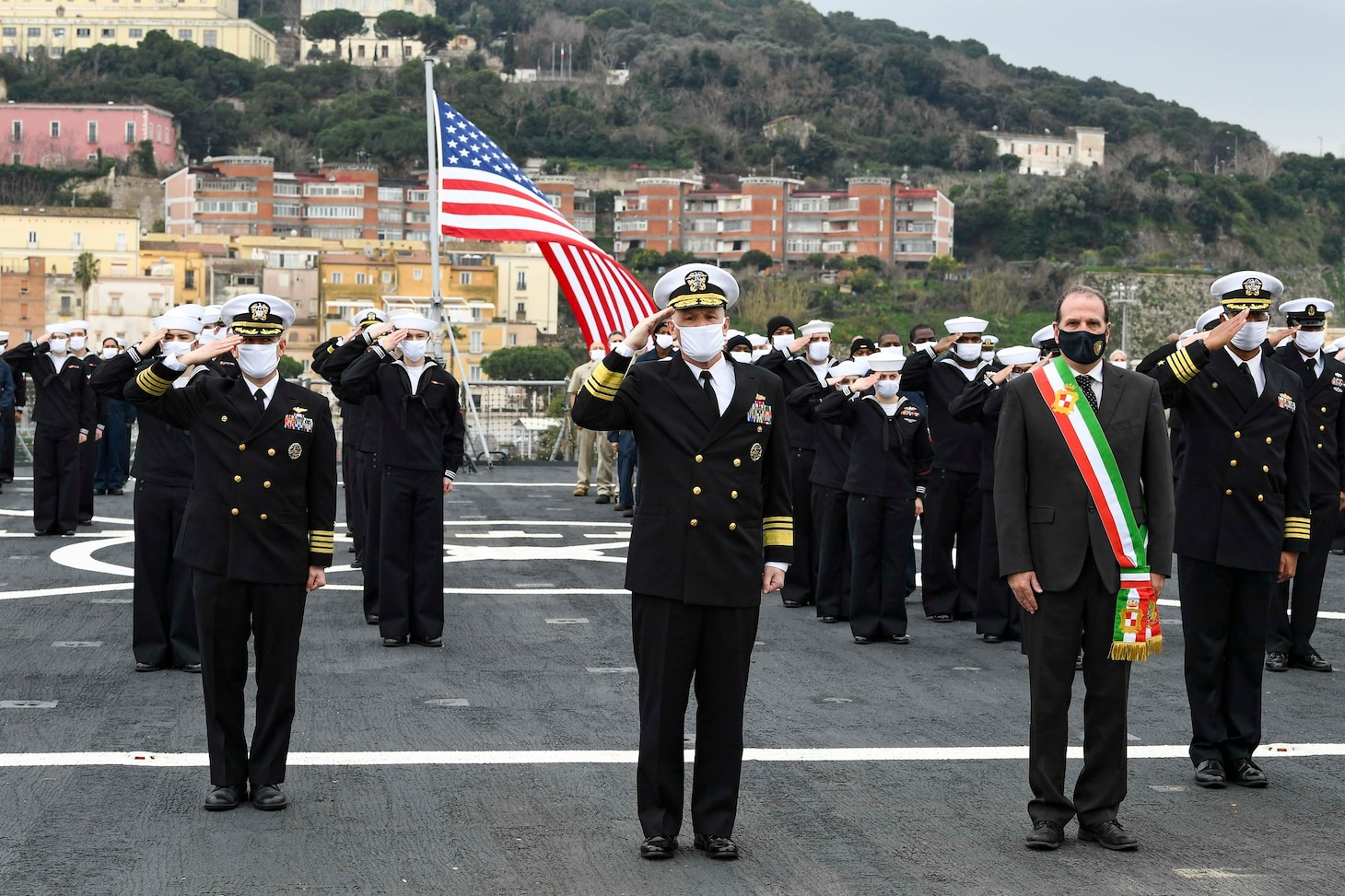 120114-N-XT273-0030 GAETA, Italy (Jan. 14, 2021) Capt. Dave Pollard, USS Mount Whitney commanding officer, left, Vice Adm. Gene Black, Commander, U.S. Sixth Fleet, center, Cosmo Mitrano, Mayor of Gaeta, and the crew of the U.S. Sixth Fleet command and control ship USS Mount Whitney (LCC 20) stand in formation during the ship's 50th anniversary celebration, Jan. 14, 2021, in Gaeta, Italy. U.S. Sixth Fleet, headquartered in Naples, Italy, conducts the full spectrum of joint and naval operations, often in concert with allied and interagency partners, in order to advance U.S. national interests, security and stability in Europe and Africa. (U.S. Navy photo by Chief Mass Communication Specialist Justin Stumberg/ Released)