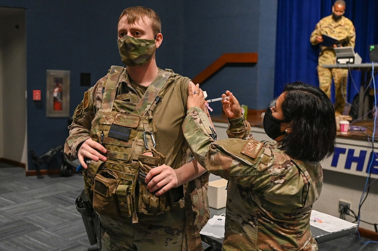 Senior Airman Christian Cardwell, 45th Security Forces Squadron Defender, recieves a COVID-19 vaccine at Patrick Space Force Base, Fla., Jan. 14, 2021. The 45th Medical Group administered the first round of the vaccine in accordance with the Department of Defense's COVID-19 vaccine distribution plan. (U.S. Space Force Photo By Airman First Class Thomas Sjoberg)