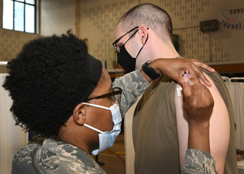 Tech. Sgt. Jordan Swaner, 66th Medical Squadron noncommissioned officer in charge of diagnostic imaging, receives a COVID-19 vaccination from Staff Sgt. Tyler Watkins, 66th Medical Squadron noncommissioned officer in charge of immunizations clinic at Hanscom Air Force Base, Mass., Jan. 14. (U.S. Air Force photo by Todd Maki)