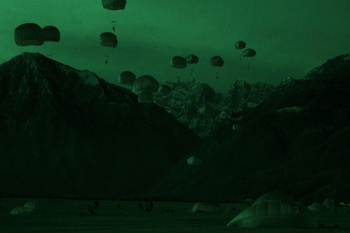 Soldiers freefall wearing parachutes near mountains.