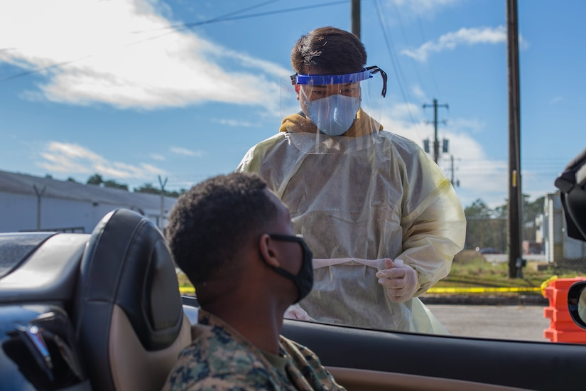 A Navy seaman wearing personal protective equipment stands on the driver's side of a vehicle and talks to a service member who is sitting in his vehicle.