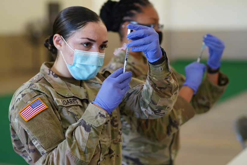 Two soldiers wearing face masks and gloves use syringes to draw medicine from a small bottle.