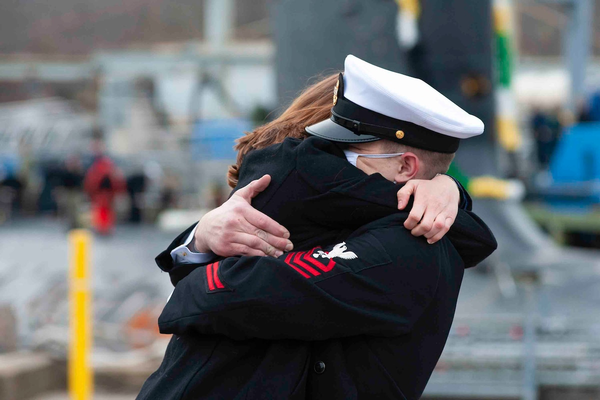 A sailor hugs a woman in a tight embrace.